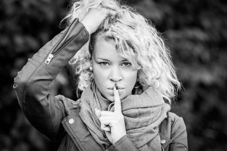 Portrait of young woman with finger on lips standing at park