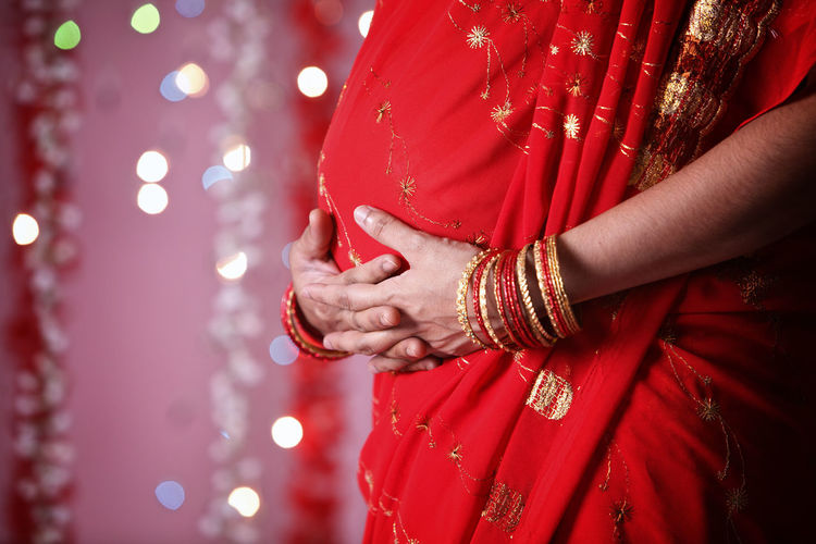 Midsection Of Pregnant Woman In Red Sari During Diwali