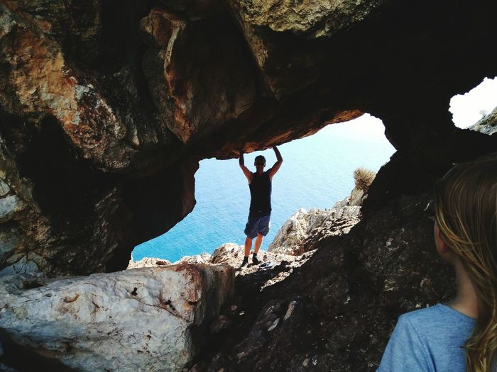 Rear view of friends on cliff against sea