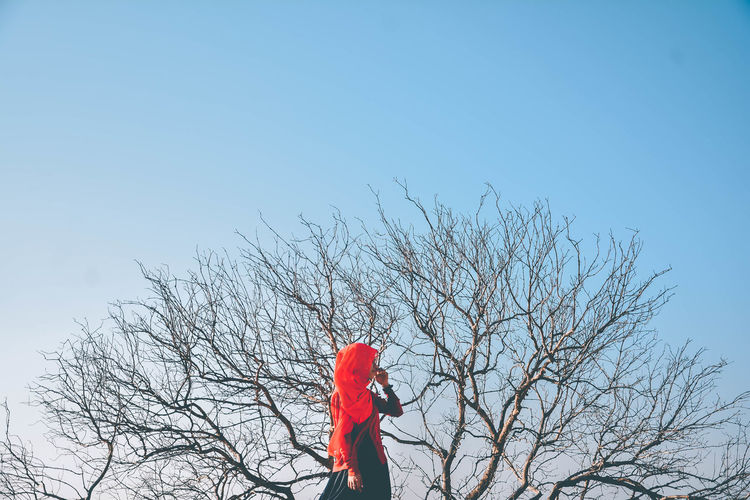 Woman standing by bare tree against clear blue sky