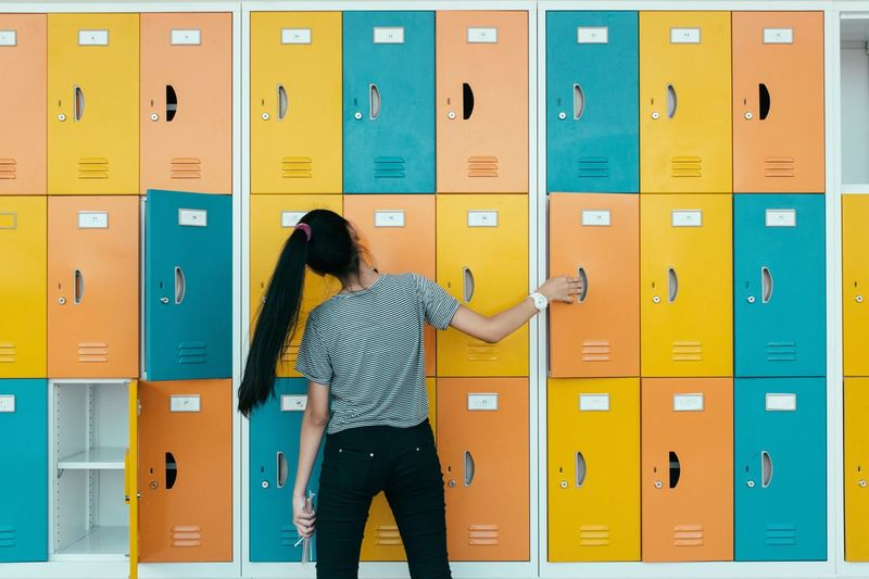 Rear view of young woman against multi colored lockers