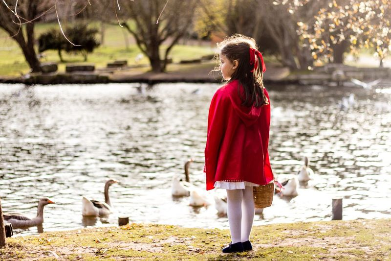Little Red Riding Hood Park Duck Full Length Outdoors One Person Brown Hair Day Standing Water Red Long Hair Lake Portrait Tree Nature Real People Animal Themes