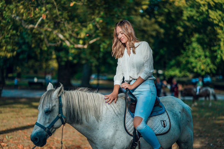Full length of woman riding horse