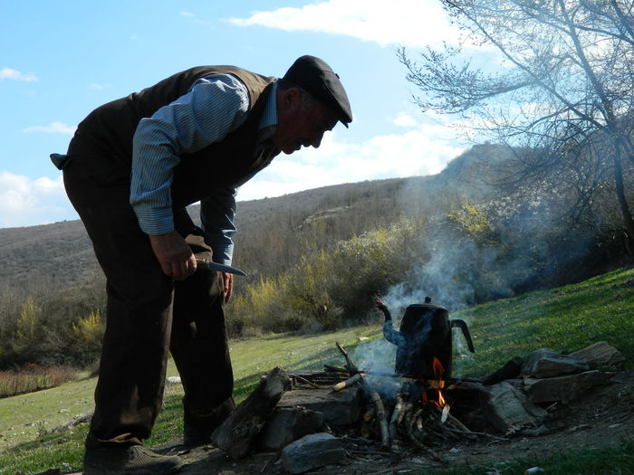 Man making fire on pasture