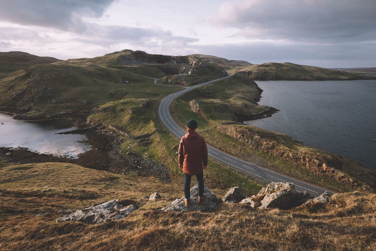 Rear view full length of man standing on mountain against empty road