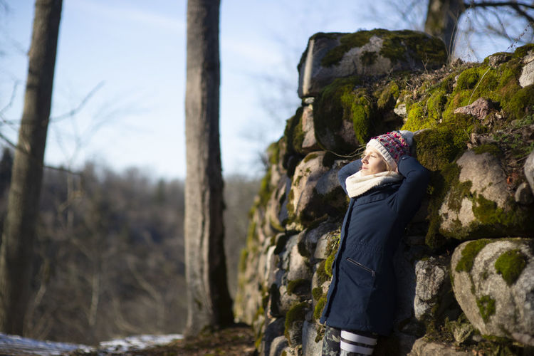 Side view of woman leaning on rocks