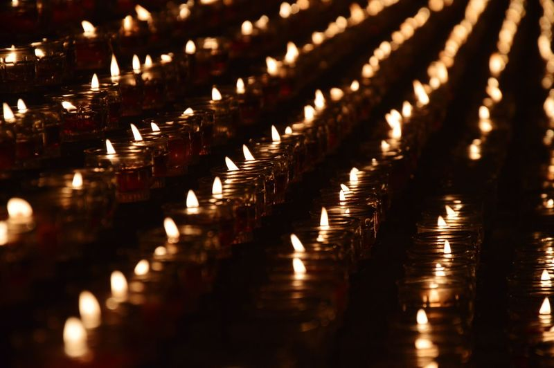Close-up of illuminated candles in temple
