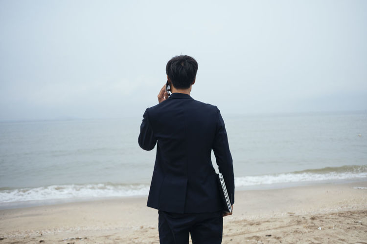 Rear view of man standing on beach
