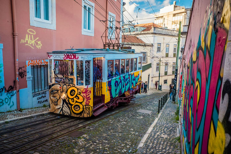 Lisbon Tram Street Art/Graffiti Tram Architecture Art And Craft Building Building Exterior Built Structure City Creativity Day Direction Footpath Graffiti Mode Of Transportation Multi Colored Mural No People Outdoors Residential District Street Street Art The Way Forward Track Transportation The Traveler - 2018 EyeEm Awards #urbanana: The Urban Playground