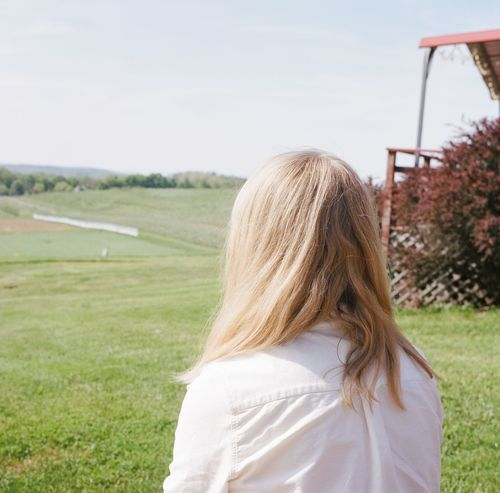 Acre Blond Hair Blonde Day Farm Farmland Field Focus On Foreground Grass Green Kodak Kodak Portra Leisure Activity Long Hair Medium Format Medium Format Film One Person Outdoors Real People Rear View Red Shallow Focus Spring Wavy Hair White
