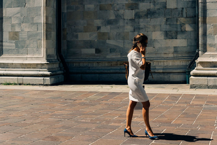Full length of woman talking on mobile phone while walking on walkway