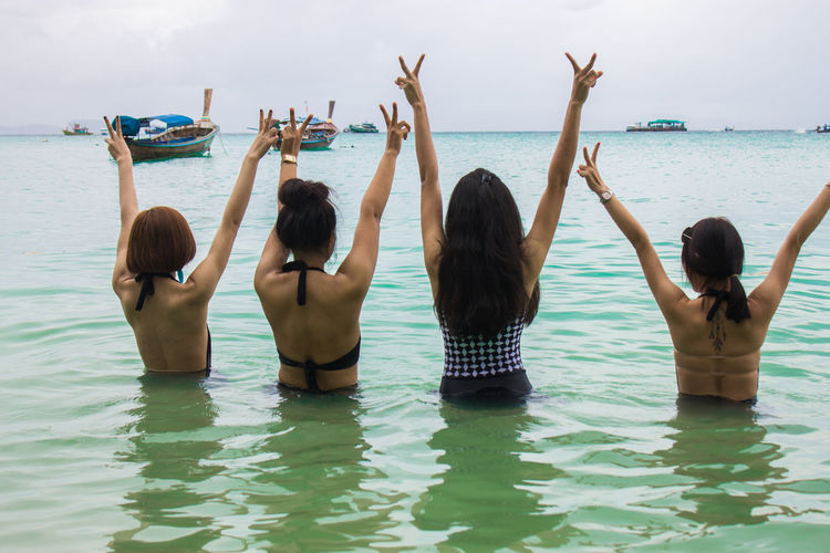 Sea Adult Arms Raised Day Group Of People Hairstyle Holiday Human Arm Leisure Activity Lifestyles Nature Outdoors People Real People Rear View Sea Sky Togetherness Trip Vacations Water Women