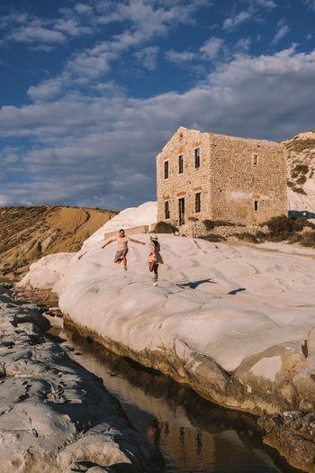 People walking on rocks against the sky