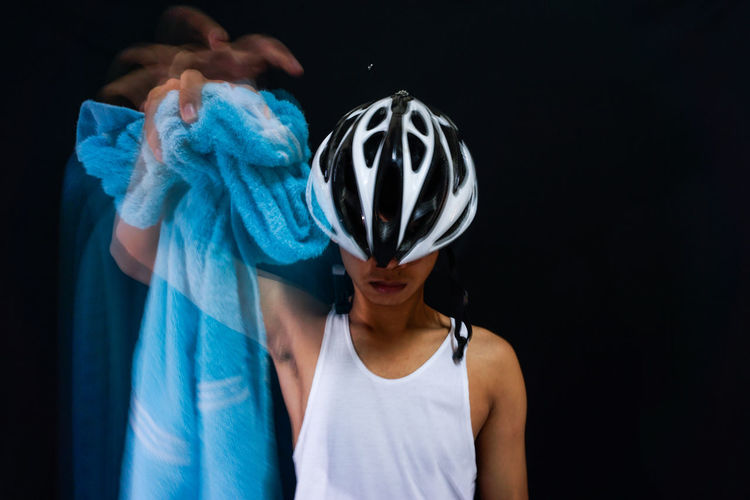 Multiple exposure image of man holding towel and wearing cycling helmet against black background