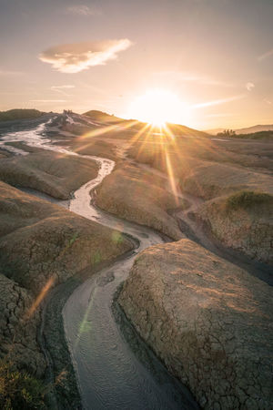 Mud river flows as Sun sets at Berca Mud Volcanoes in Romania Beauty In Nature Day Lens Flare Mud River Mud Volcanoes Nature No People Outdoors Romania Scenics Sky Sun Sunbeam Sunlight Sunset Tranquil Scene Tranquility Water Lost In The Landscape Perspectives On Nature