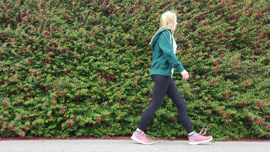 Low Angle View Of Woman Walking Against Hedge In Park