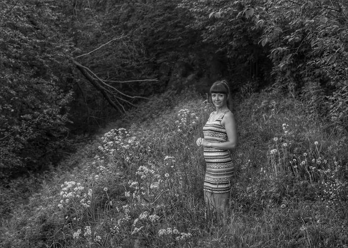 Portrait of woman standing on field amidst plants