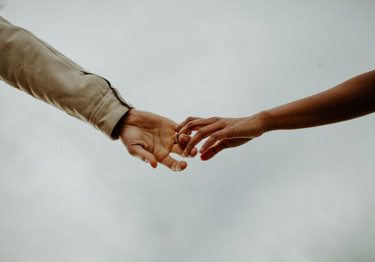 Cropped image of couple holding hands against clear sky