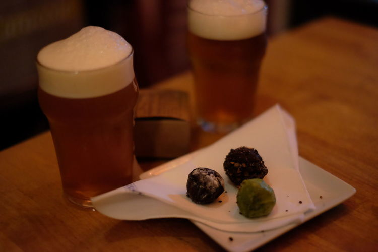Close-Up Of Sweet Food And Beers Served On Table