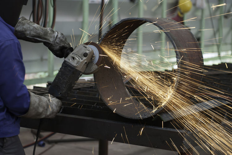 Low angle view of man working on metal in factory