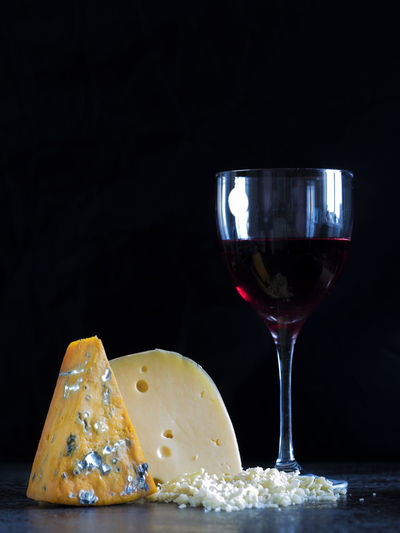 Fresh pieces of cheese (roquefort, Maasdam) and wine on the stone table Alcohol Black Background Cheese Close-up Cracker Drinking Glass Food Fresh Freshness Gourmet Healthy Eating Indoors  Maasdam No People Pieces Red Wine Roquefort SLICE Stone Table Wine Wineglass