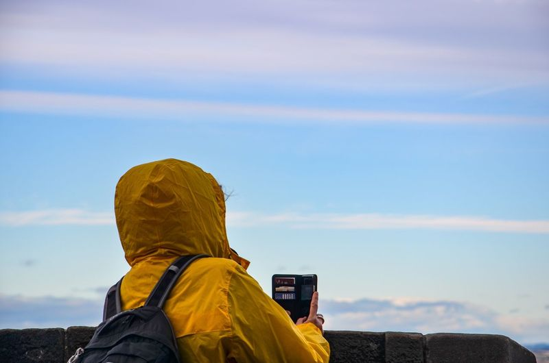 Rear view of person in yellow raincoat photographing against sky