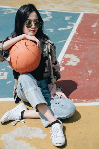 Smiling young woman with basketball sitting on court