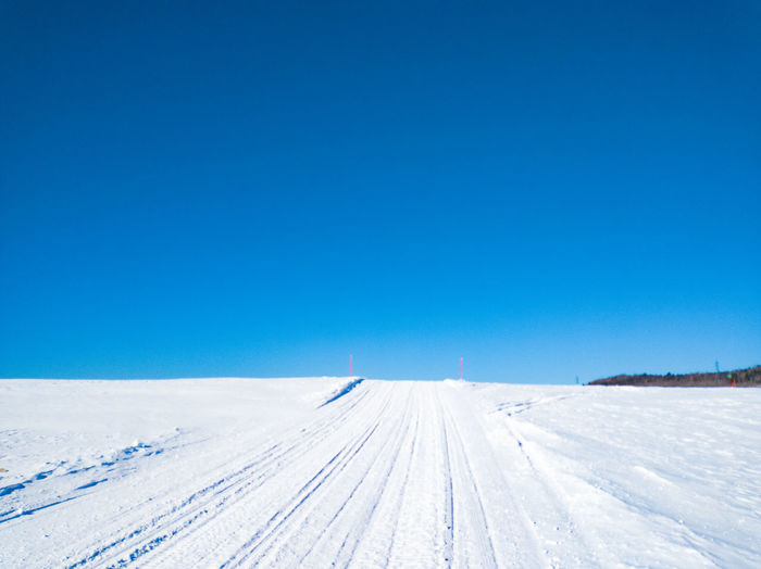 Snow covered land against clear blue sky