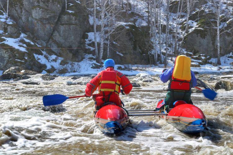 People Kayaking In River During Winter
