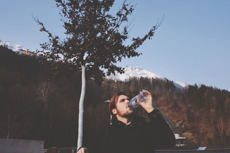 Young Man Drinking Water Against Forested Mountain