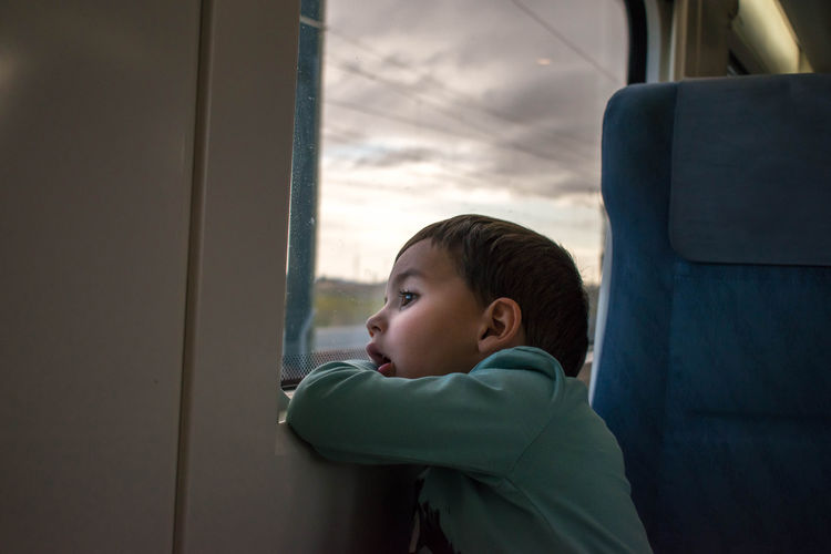 Boy looking through window of train