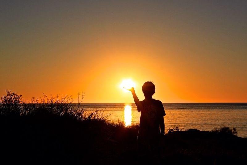 Boy cupping hand under sun