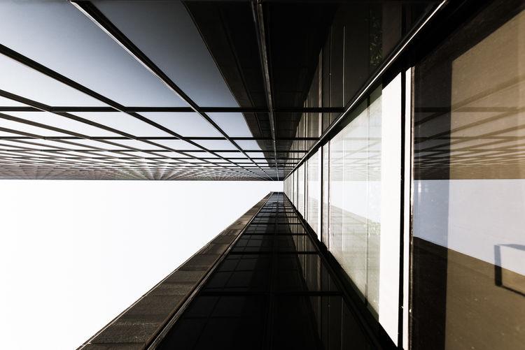 Directly below shot of bridge against sky in city