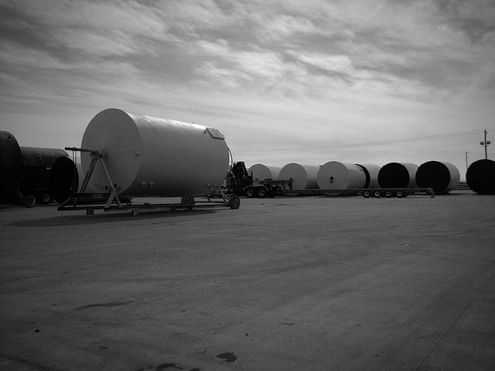 Oil tanks at industry against cloudy sky