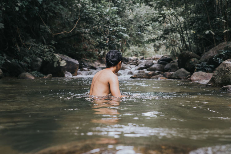 Full length of shirtless man on rock in forest