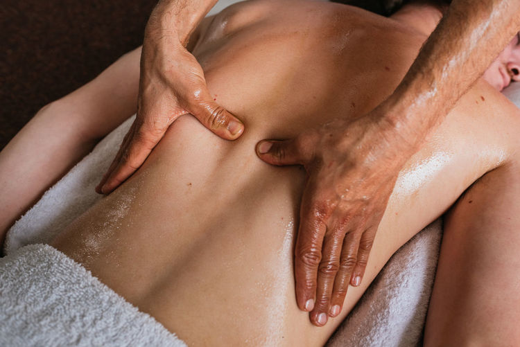 Cropped hand of aromatherapist massaging man