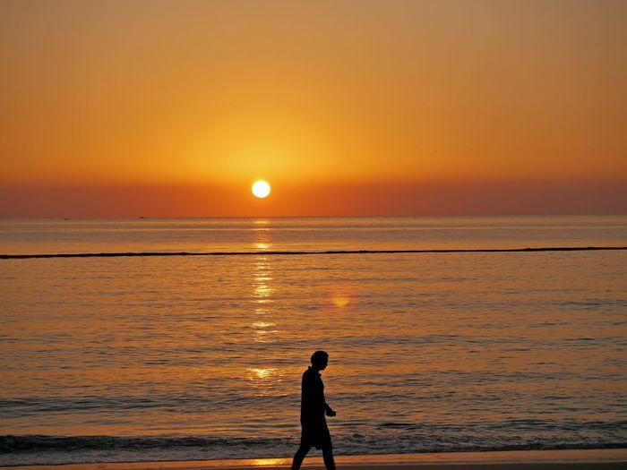 Silhouette man walking at beach during sunset