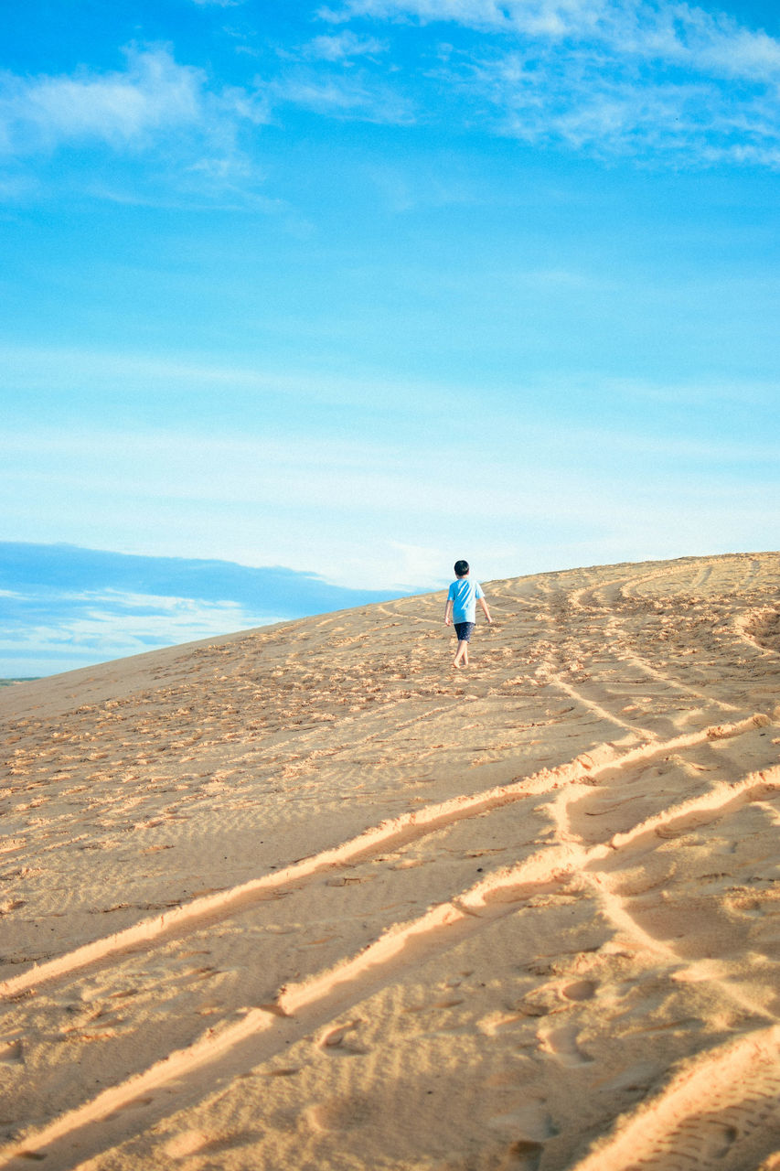 tranquil scene, sky, sand, rear view, nature, beach, scenics, sea, one person, walking, day, beauty in nature, tranquility, outdoors, vacations, real people, blue, full length, horizon over water, landscape, sand dune, people