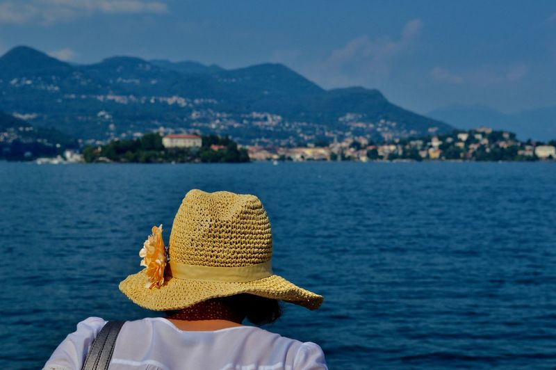 Rear view of woman wearing hat against sea