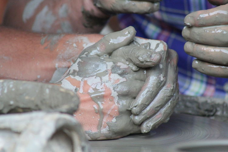 Cropped Hands Shaping Pots At Workshop