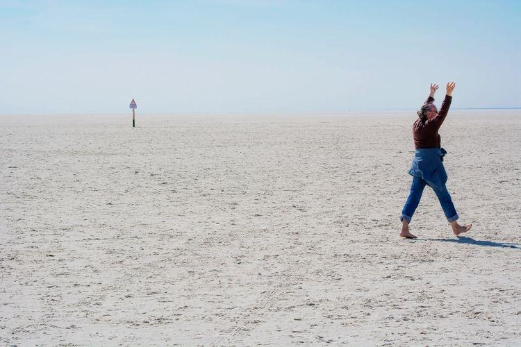 Man walking on sand at beach