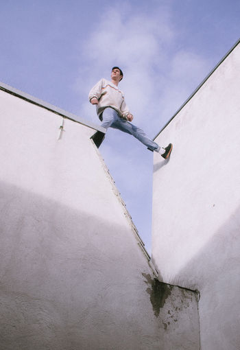Low angle view of man against wall against sky