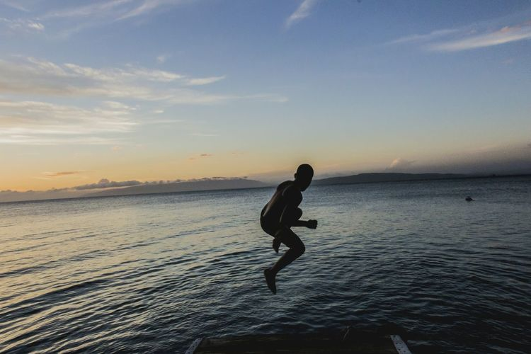 Silhouette Boy Jumping Over Sea Against Sky