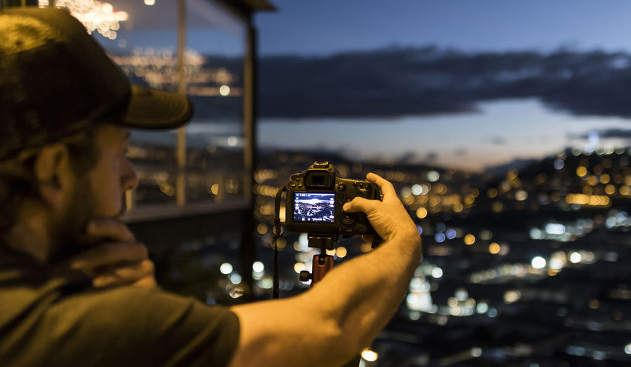 Young man photographer with cap taking pictures of the city of Quito Ecuador during sunset with the lights of the city in background Technology Photography Themes Wireless Technology Holding Activity Headshot Photographing Architecture One Person Portrait Illuminated Communication Focus On Foreground Mid Adult Outdoors Cityscape Sunset Bokeh Quito Ecuador Camera - Photographic Equipment Lights On Cap Capital Cities  Adult