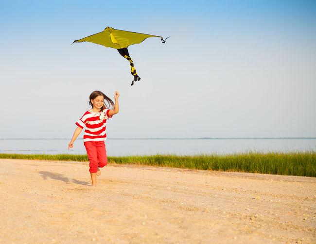 Full length of boy flying kite against sky