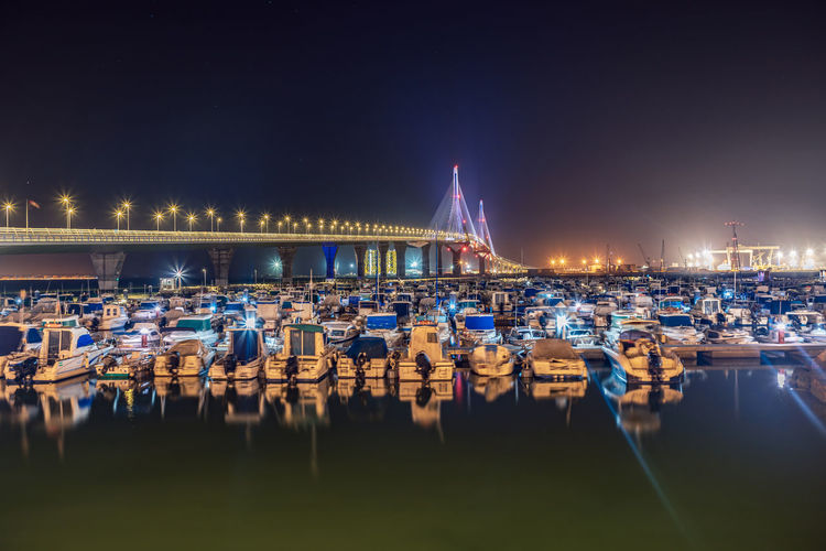 High angle view of boats moored at harbor at night