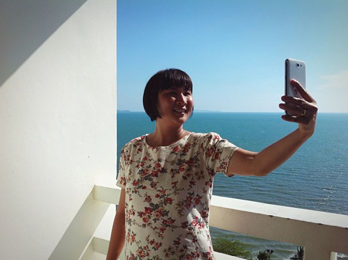 Happy young woman taking selfie against wall