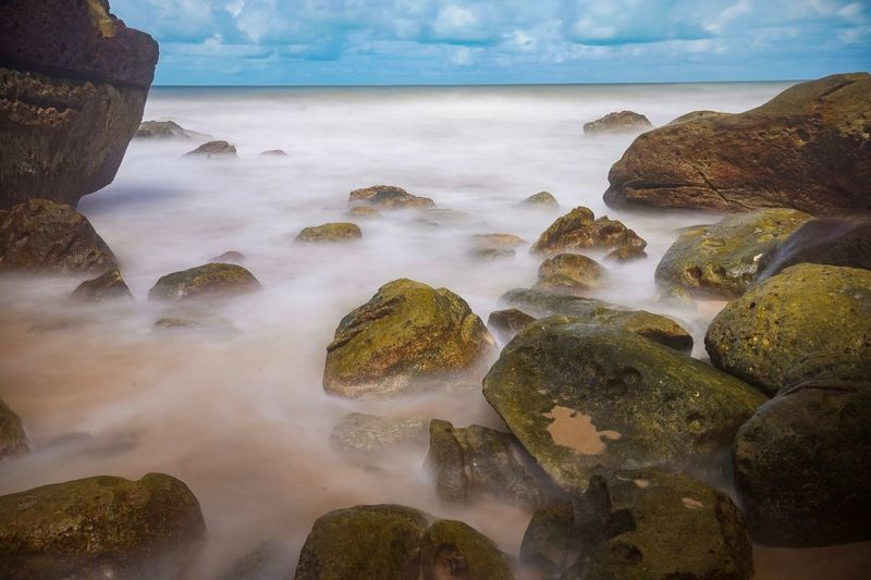 A scenic view of a long exposure shot at a stony beach in Kuching, Sarawak Water Sea Sky Land Beach Scenics - Nature Beauty In Nature Cloud - Sky Rock - Object Solid Horizon Over Water Horizon Rock Nature Tranquility Tranquil Scene No People Blue Island Outdoors