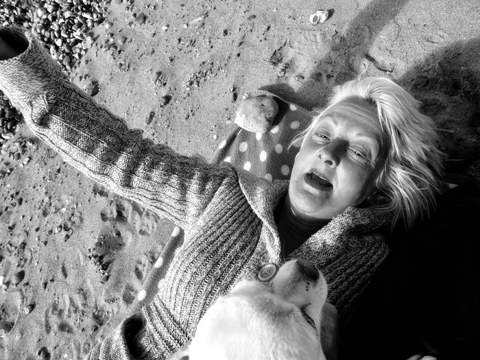 High Angle View Of Woman With Dog Lying At Beach