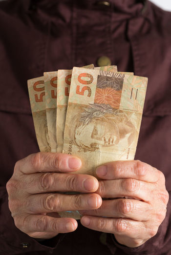 Close-up of man holding paper currencies